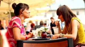stock-footage-two-female-friends-chatting-in-restaurant-outdoors-camera-stabilizer-shot
