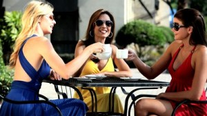 stock-footage-three-sophisticated-female-friends-meeting-at-outdoor-cafe-after-a-successful-shopping-trip
